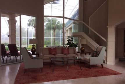 Bonita Bay Estate Home with glass walled dining room overlooking 10,000 gallon pond.