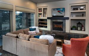 Living room with fireplace, tan sectional, and red arm chair
