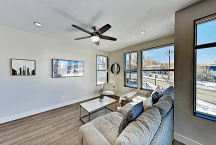 Main floor living room with beige sectional and wall art